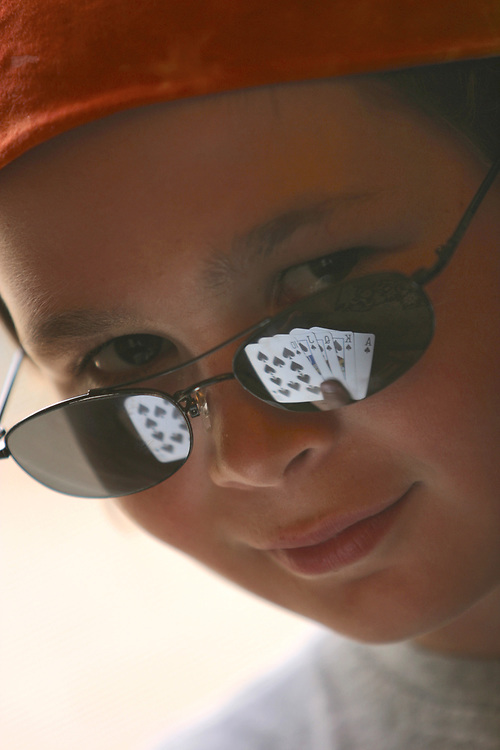 Young boy with royal straight flush reflected in his glasses.