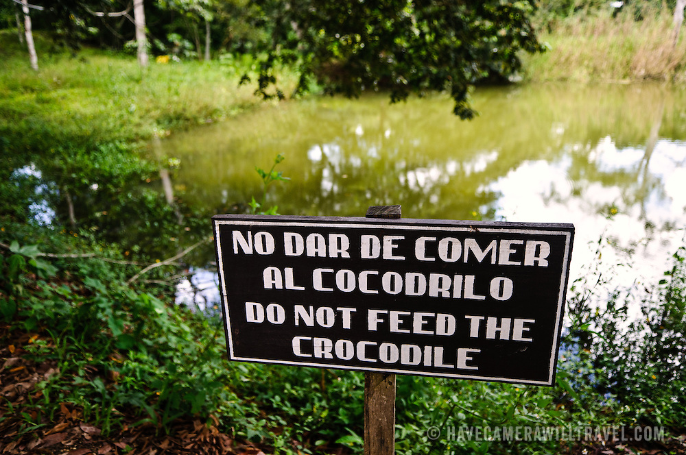 A sign warns visitors not to feed the crocodiles in the Tikal Maya ruins in northern Guatemala, now enclosed in the Tikal National Park. Set deep in the jungle, Tikal has abundant wildlife of jaguars, howler monkeys, spider monkey, coatimundis, toucans, and ocellated turkeys.