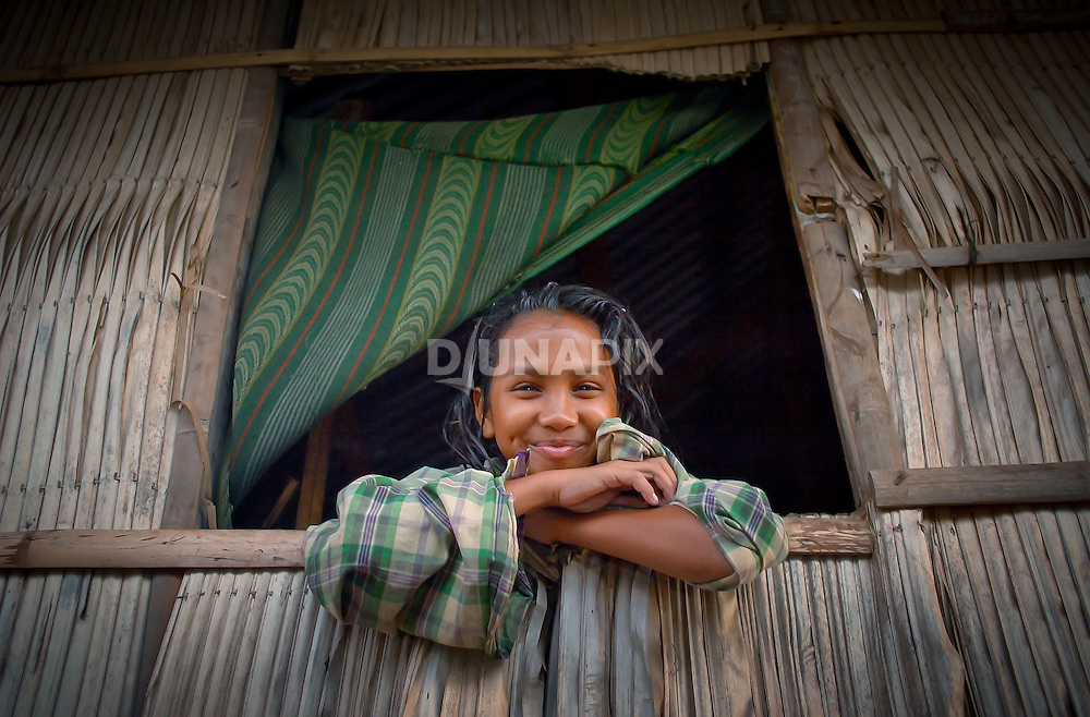 Pretty girl frames herself in window, Papagaran island, Komodo National Park