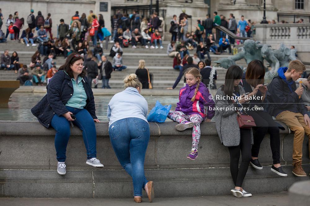Large ladies and child in Trafalgar Square, London.