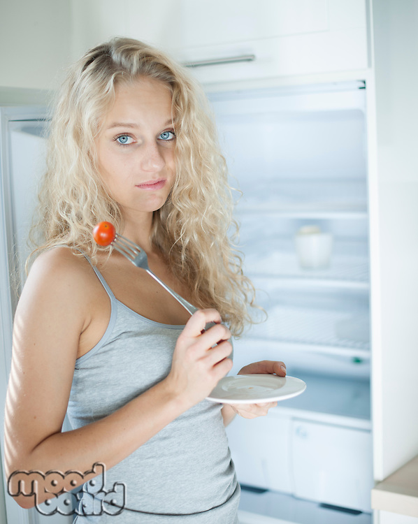 Portrait of sad woman having cherry tomato in kitchen