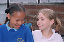 Two primary school girls standing together in playground smiling,