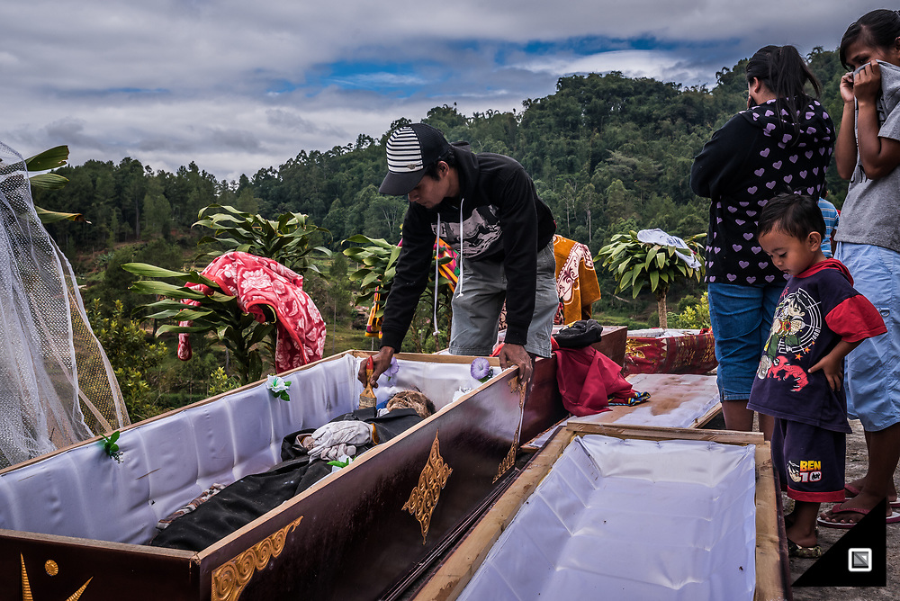Indonesia - Sulawesi - Tana Toraja. Graveyard in Panggala, Rindigallo.<br /> <br /> Grandpa &quot;Ne Pua&quot;, passed away with 85 years. He has been buried in his favorite suit, together with hes favourite belongings, like the mobile phone and glasses. <br /> <br /> The Ma'Nene Ritual is about to start. The coffins have been dragged out of the family's mausoleum. After cleaning the dead body, clothes will be changed before having a sunbath. Rising to Puya (Heaven) also means to enter the afterlife. And, to continue with the living standards one is used to when being on earth. That&rsquo;s why it is customary for the Torajans to put a gift in the coffin of their ancestors before locking it into a family mausoleum or the traditional stone grave. For some, a bracelet or a watch would do, while the highest cast might even bury a diamond with their loved ones. Nowadays, many are afraid their gifts get stolen. Local police authorities are even investigating cases of stolen mummies. The rumor spread that there&rsquo;s a high demand from foreign antique-collectors based in Bali. Supposedly, they&rsquo;re hiring thieves from the area to steel bodies for their private exhibitions. Not to forget about the missing baby mummies who apparently are used for occult medicine.