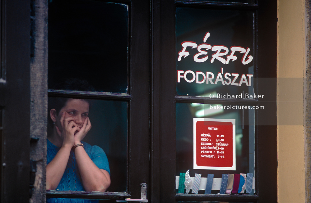 A Hungarian lady in deep thought peers through a 1990s window of a hairdressing salon in the Hungarian capital, on 18th June 1990, in Budapest, Hungary.