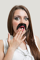 Portrait of shocked young woman with fake moustache over gray background