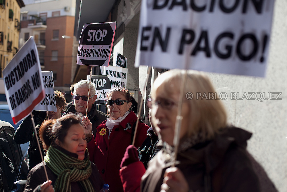 Anti-Eviction supporters hold signs that read (L-R) 'No to the dictatorship of the banks', 'Stop evictions' and 'Lieu of payment'.month on February 22, 2012. Cabrera Maza, a 48-year-old immigrant form Ecuador, lives with her daughter in Madrid and started paying her mortgage on 2006 but then underwent serious health problems that let her in a permanent incapacity. Unable to work and earning a monthly pension of 600€ for her incapacity, she could not afford to pay her mortgage, which had increased from 800€ to 1890€ and stopped paying it on June 2010. She was served her first eviction notice in June 2011. The Organization Anti-evictions supported her and she finally got permission to stay at her appartment for another month. She is claiming a lieu of payment to the bank, so she can go back to her country without a debit of 250.000€, where her family will take care of her and her illness.