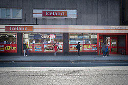 © Licensed to London News Pictures. 26/03/2020. London, UK. Shoppers socially distance while they queue outside a branch of Iceland in Greenwich . The Government has announced a lockdown to slow the spread of Coronavirus and reduce pressure on the NHS. Photo credit: George Cracknell Wright/LNP