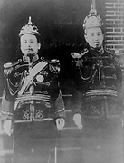 Kojong, Emperor of Korea (1852-1919) and the Crown Prince Yi Wang. Emperor and prince in uniform, standing and facing forwards.