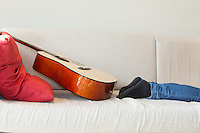 Low section of man's leg with guitar kept on sofa