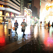 Shanghai, China: Shops and pedestrians on a cold rainy evening in Nanjing Xi Lu.  Jose More Photography