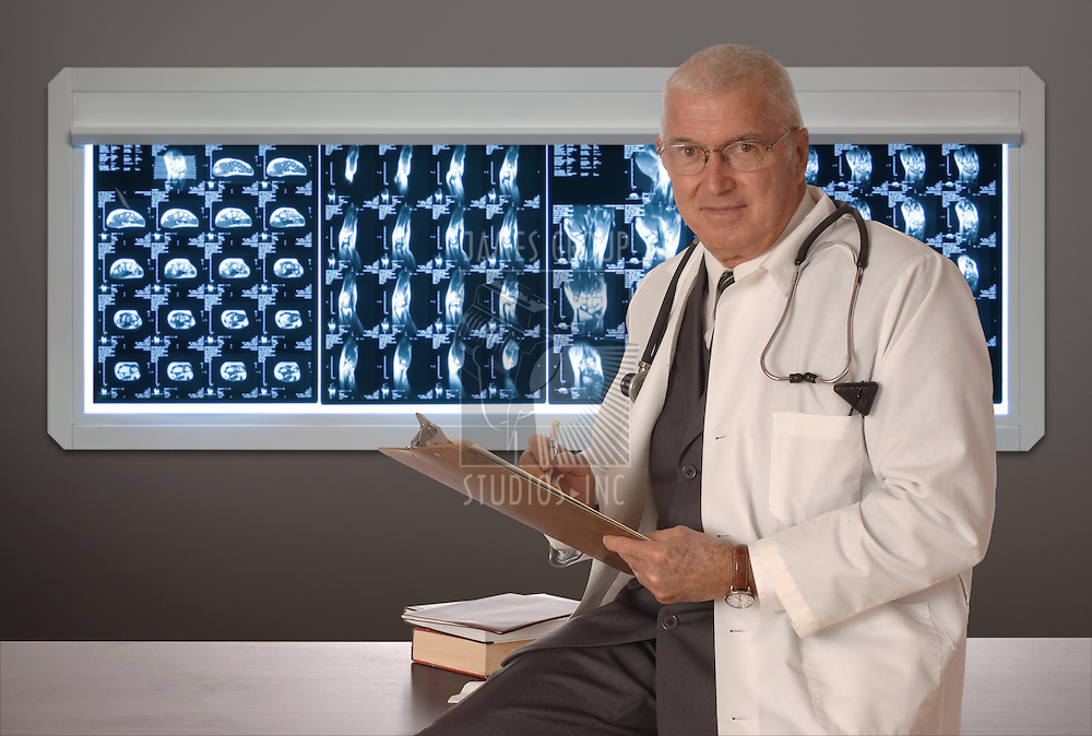 Mature doctor sitting on a desk with MRI films in the background