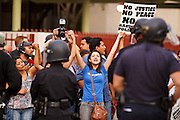 04/25/12-  Andy DeLisle.Protestors chant at police after being pushed back to the sidewalk in the March for Justice against SB 1070 on Wednesday April, 25 2012 in Phoenix, AZ.