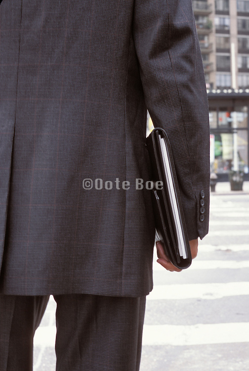Close up of a business man walking with a folder under his arm