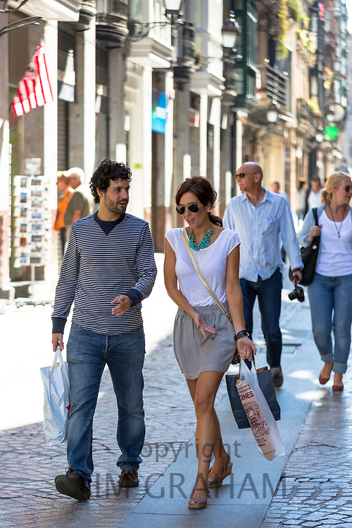 Young couple strolling in Calle de Bidebarrieta in Bilbao, Spain