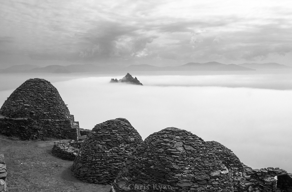 Beehive huts on Skellig Michael; Little Skellig peaking out of clouds in background; County Kerry, Ireland