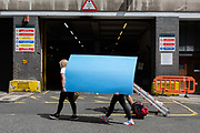 Staff with visual merchandising supplier 'Bright Leaf' carry blue boards and materials  back to their West End premises, on 24th July 2020, in London, England.