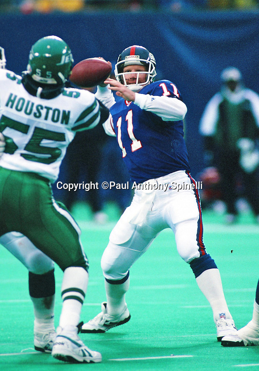 New York Giants quarterback Phil Simms (11) throws a pass while pressured by New York Jets linebacker Bobby Houston (55) during the NFL football game against the New York Jets on Oct. 31, 1993 in East Rutherford, N.J. The Jets won the game 10-6. (©Paul Anthony Spinelli)