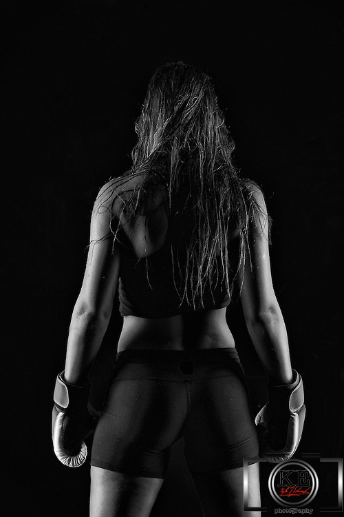 A black and white rear silhouette of a female boxer.