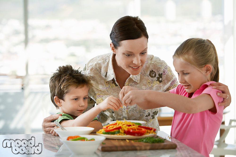 Mother Helping Children Prepare a Meal in kitchen