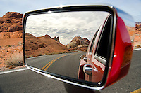 Side view mirror reflection displays the fiery red rock formations of Valley of Fire State Park in Nevada, USA.
