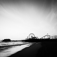 Santa Monica Pier black and white photo. Santa Monica Pier is a landmark that has an amusement park with a ferris wheel, roller coaster, restaurants, and other attractions.