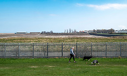 "Cockenzie, UK. 14 April, 2018. Dog walker at site of the former Cockenzie power station in East Lothian, Scotland. A row has begun over concerns about the Scottish government's decision to ""call in"" a planning application by Red Rock Power to build a renewable energy sub-station on the site. Red Rock Power, part of China's largest state-owned investment fund, the State Development and Investment Corporation (SDIC), wants the the sub-station to allow it  to feed power from the Inch Cape offshore wind farm, near Angus, into the national grid."