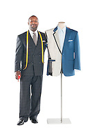 Portrait of a male tailor standing next to a mannequin