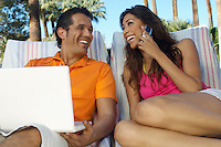 Couple with laptop and mobile phone relaxing in deckchairs