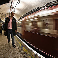A man gets out of a train in a London Underground Station.