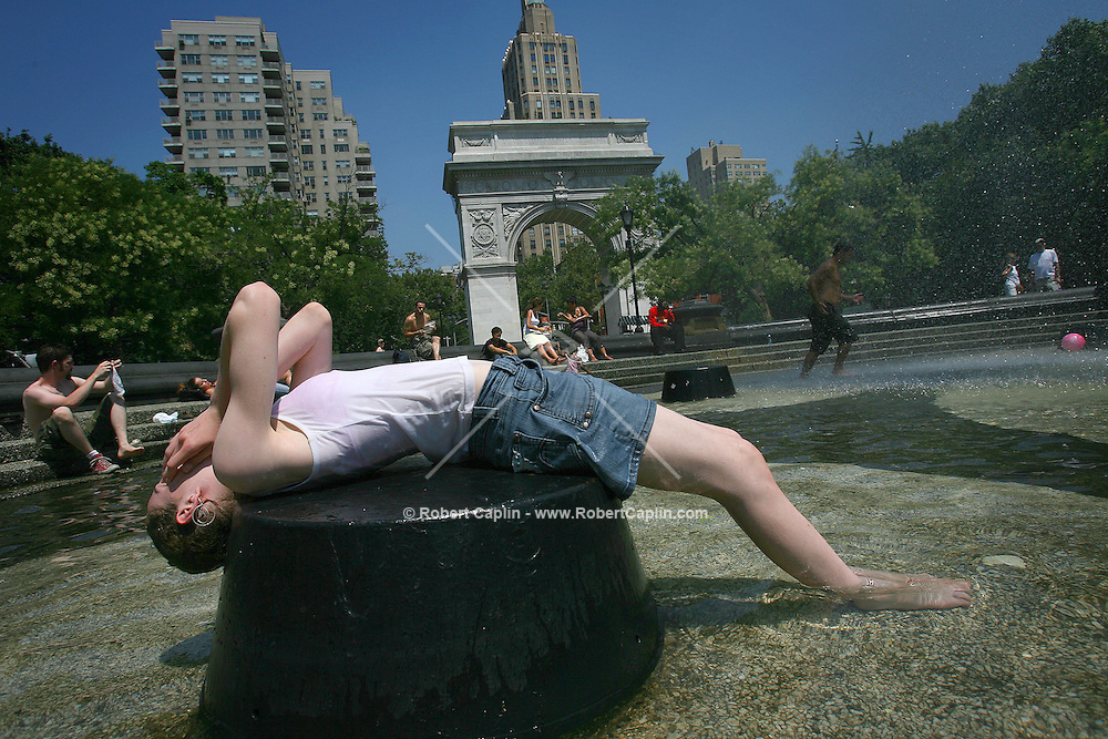 Lucy Stickland, on holiday from England, cools off in the public fountain at Washington Square Park in Manhattan. 8/3/06.