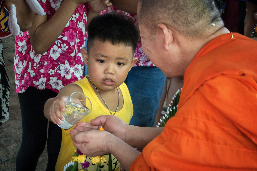 A young man pours water on the hands of a monk, which is a blessing as well as wishing prosperity and happiness in the coming year at a rural Songkran festival.