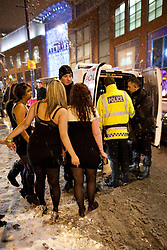 "© under license to London News Pictures. 18/12/2010 as snow blizzards hit Manchester revellers continue their ""Mad Friday"" night out. Despite the freezing conditions, some still managed barefoot. These girls are concerned about their friend who's just been arrested following a fight."