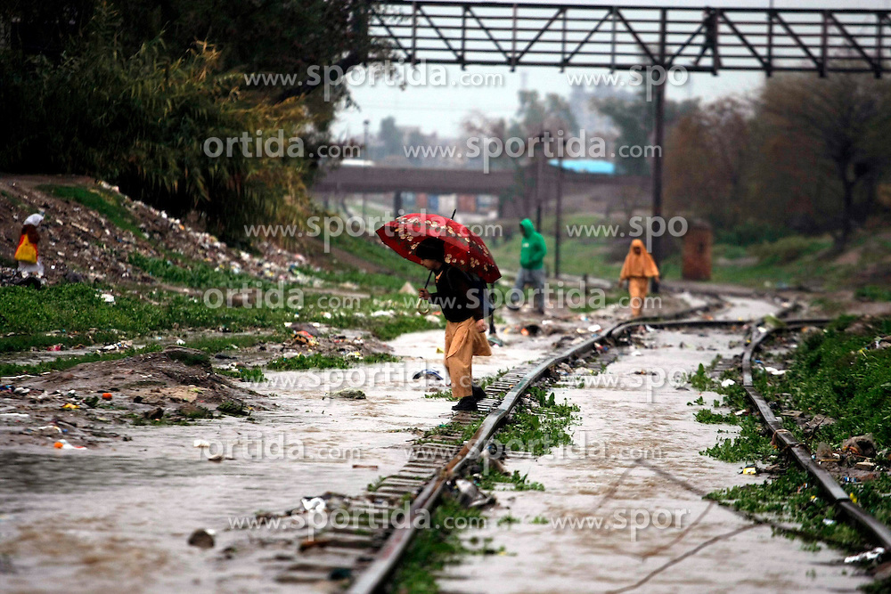 A school boy crosses a waterlogged railway track after heavy rain in northwest Pakistan's Peshawar, Feb. 25, 2015. At least two women were killed as a roof of a house collapsed in Peshawar. Heavy rains have wreaked havoc in different areas of Kashmir, Khyber Pakhtunkhwa and Gilgit-Baltistan on Wednesday, local media reported. EXPA Pictures &copy; 2015, PhotoCredit: EXPA/ Photoshot/ Umar Qayyum<br /> <br /> *****ATTENTION - for AUT, SLO, CRO, SRB, BIH, MAZ only*****