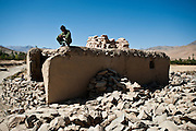 An Afghan local policeman crouches atop a makeshift police outpost in the remote Nerkh Valley.