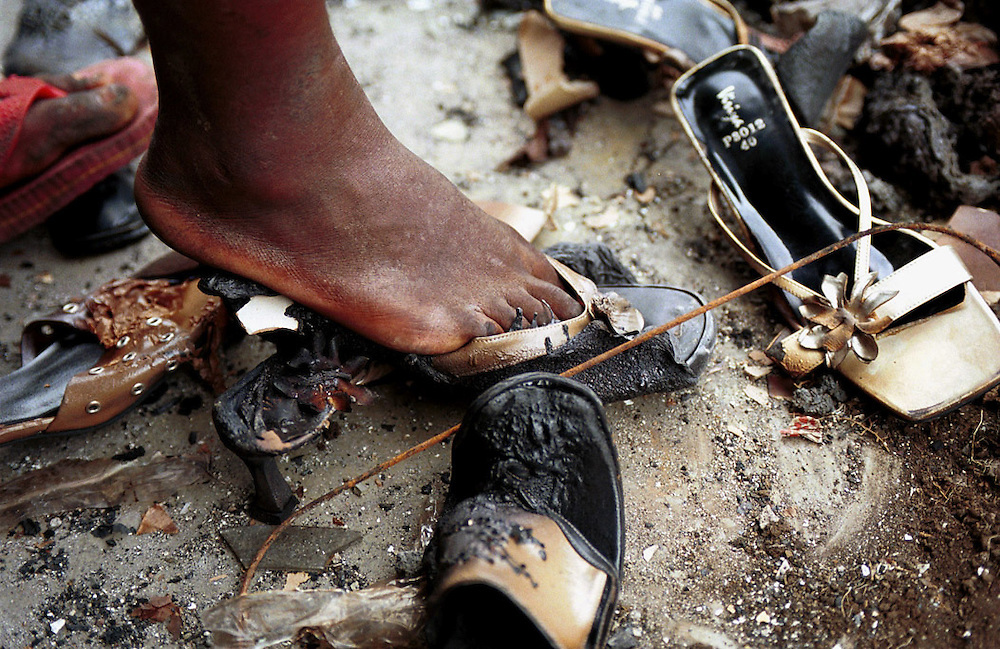A girl tries on a burnt shoe, salvaged from a boutique which was destroyed in the business district of Goma, Democratic Republic of Congo. Goma, a city of 400,000 people was engulfed in lava from the Nyiragongo volcano which erupted on 17/1/02.