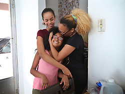 Nerys Medina hugs her daughters Glennys (left) and Karelys, at their home in the town of San Lorenzo as they package to leave Puerto Rico on October 2. After deciding against their will to leave since their house got damaged, her husband Carlos Rolâ¤â€n, a financial planner is jobless and their daughters' schools are closed for an unknown amount of time forcing many Puerto Ricans to fly to the U.S. after Hurricane Maria, (category 4) passed through Puerto Rico devastating the island leaving residents without power and ways to communicate on Sept. 20. on October 02, 2017. Photo by Pedro Portal/Miami Herald/TNS/ABACAPRESS.COM