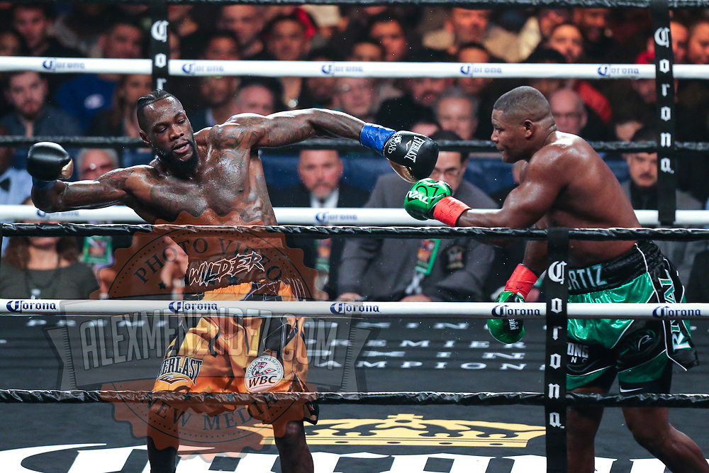 Deontay Wilder falls back after being punched by Luis Ortiz during the WBC Heavyweight Championship boxing match at Barclays Center on Saturday, March 3, 2018 in Brooklyn, New York. Wilder would win the bout by knockout in the tenth round to retain the title and move to 40-0. (Alex Menendez via AP)