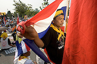"BANGKOK, THAILAND  -  March 14: A man wraps himself in the Thai flag as he joins tens of tousands of demonstrators seeking the resignation of Prime Minister Thaksin Shinawatra marched to government house on March 14, 2006 in Bangkok, Thailand. Marching several kilometers from the Grand Palace to Government House the protesters surrounded Thaksin's office chanting ""Thaksin Get Out"", as the Prime Minister threatened a state of emergency if the demonstration turned violent.  (Photo by David Paul Morris)"