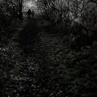 Two people walking along a narrow path in winter