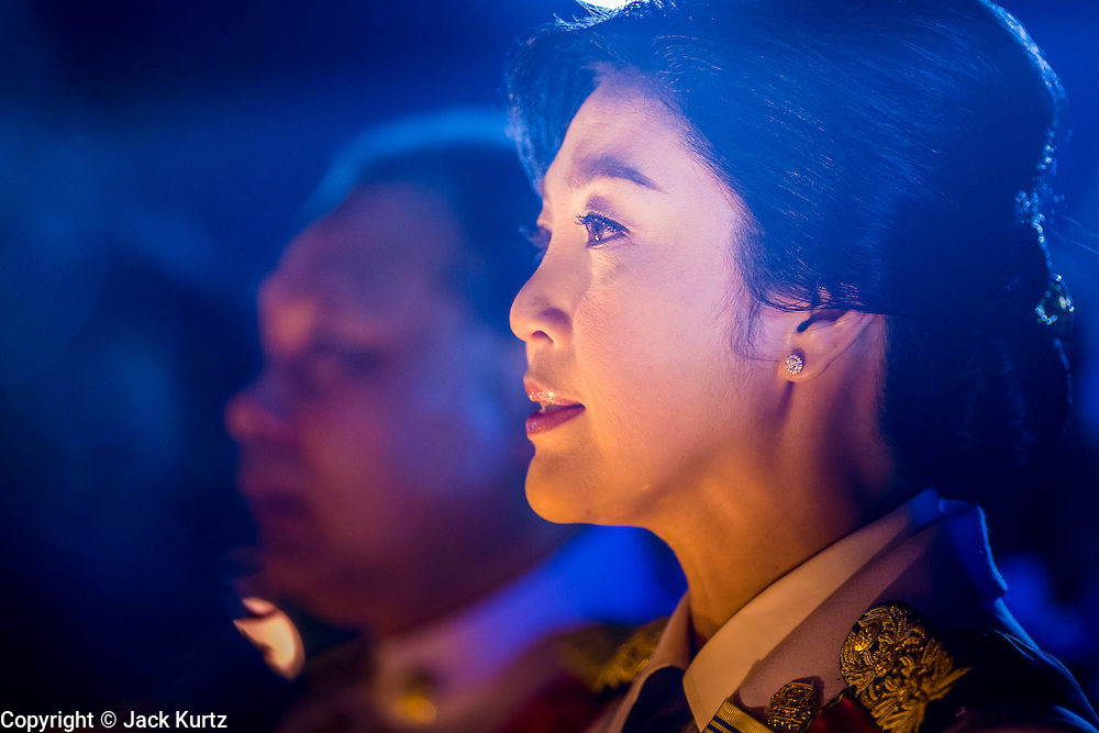 YINGLUCK SHINAWATRA, the Prime Minister of Thailand, reads a proclamation honoring the King at the celebration of the birthday of the King in Bangkok. Thais observed the 86th birthday of Bhumibol Adulyadej, the King of Thailand, their revered King on Thursday. They held candlelight services throughout the country. The political protests that have gripped Bangkok were on hold for the day, although protestors did hold their own observances of the holiday. Thousands of people attended the government celebration of the day on Sanam Luang, the large public space next to the Grand Palace in Bangkok.