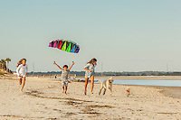 Three siblings, two sisters and their brother, run down the beach with a colorful kite in the sky above them. Their dogs run along with them.
