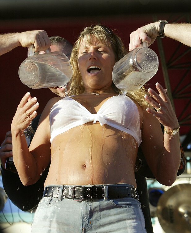 "A volunteer from the audience is doused with ice water during a ""wet t-shirt contest"" in a bar on Main Street during Bike Week in Daytona Beach,  Florida March 8, 2005. The annual ten-day event attracts motorcyclists of all varieties with over 500,000 expected this year."