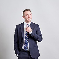 A portrait of a legal recruitment firm employee as he poses for an informal portrait in front of a neautral background at work