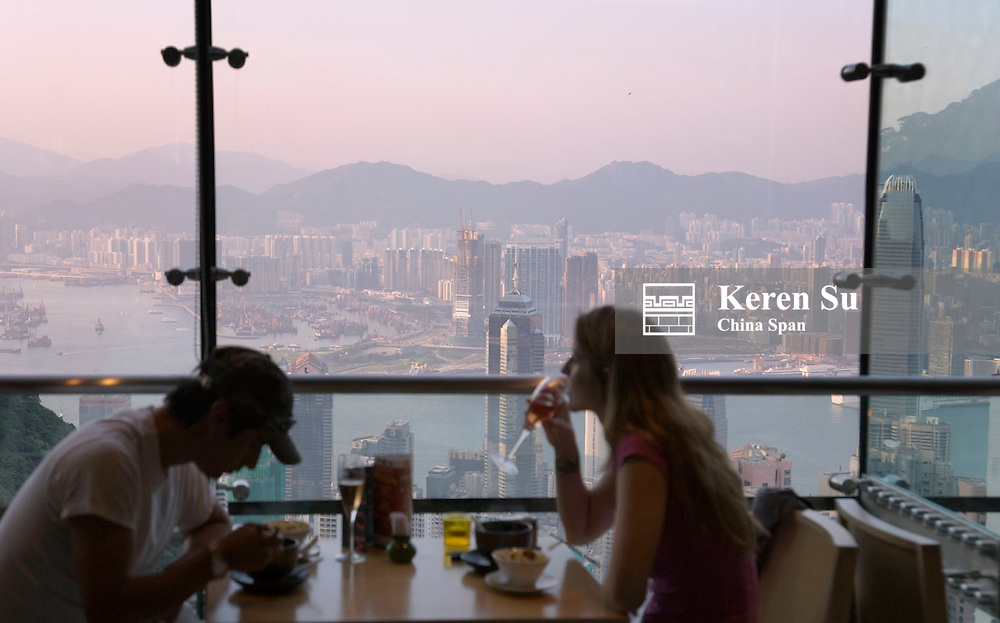 People dining in restaurant, highrises skyline outside the window, Hong Kong, China