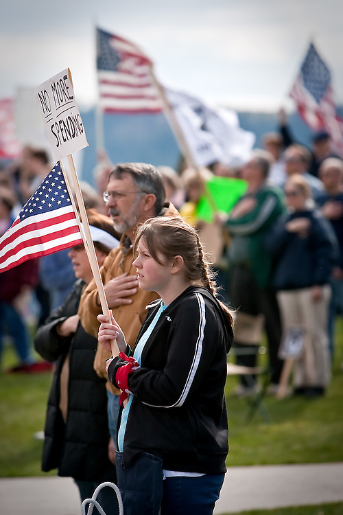 "JEROME A. POLLOS/Press..Natasha Stevens, 12, holds a sign protesting government spending while the national anthem is played at the beginning of the tax day ""tea party"" rally."