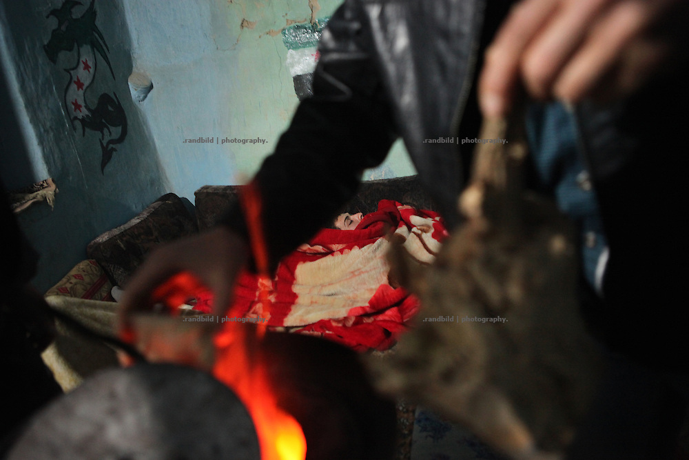 A soldier sleeps in the makeshift headquarters of the Free Syrian Army in Al Janoudiyah, Province of Idlib, Syria, while a comrade fires the stove to heat at night.