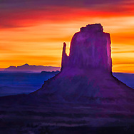 Colorful painterly rendition of a Western desert rock formation at sunset in purple, orange, red and yellow colors