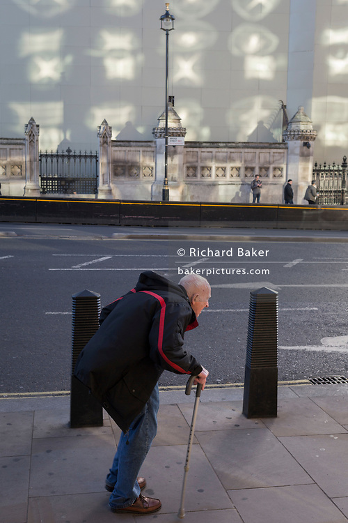 A man with poor posture walks beneath the Queen Elizabeth Tower at the Houses of parliament, currently under hoardings and scaffolding during the multi-million Pound renovation and reapir project - unusually reflected light from Portcullis House windows, on 23rd November 2017, in London England.