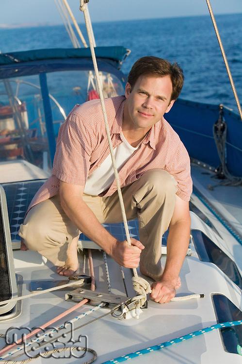 Man on Sailboat Tying Rope