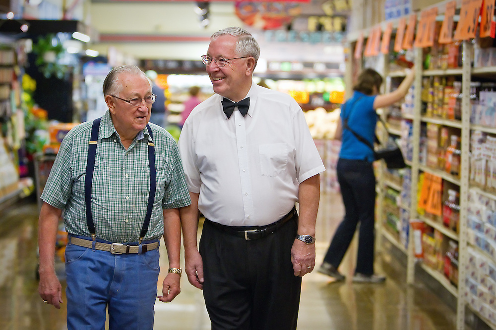 Ron McIntire, in his trademark bow tie, walks along an aisle of his Super 1 Foods store Wednesday in Hayden with his friend and customer Darwin Grant. McIntire began his grocery career in Quincy, Wash. in 1955 and has been operating his own grocery stores in Idaho since 1970.